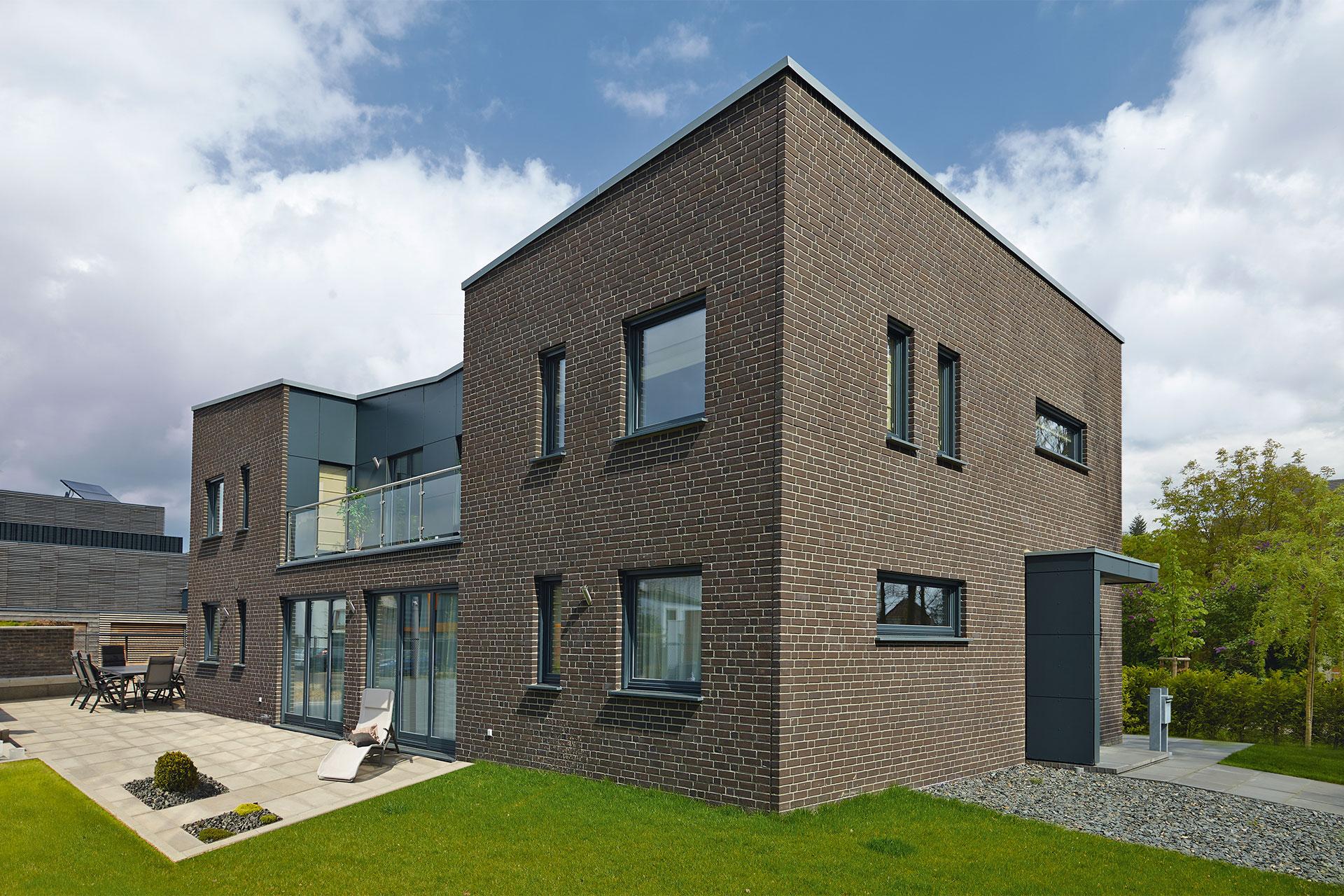 Modernes Fertighaus mit zeitgemäßer, dunkler Klinker-Fassade und ...